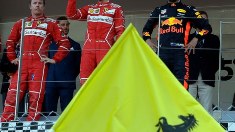 Ferrari driver Sebastian Vettel of Germany, center, celebrates with his second placed teammate Kimi Raikkonen of Finland, left and third placed Red Bull Racing driver Daniel Ricciardo of Australia after winning the Formula One Grand Prix at the Monaco racetrack in Monaco, Sunday, May 28, 2017. (AP Photo/Claude Paris)