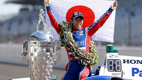 Indianapolis 500 champion Takuma Sato, of Japan, poses with the Borg-Warner Trophy during the traditional winners photo session on the start/finish line at the Indianapolis Motor Speedway in Indianapolis, Monday, May 29, 2017. (AP Photo/Michael Conroy)
