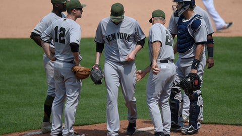 New York Yankees starting pitcher Jordan Montgomery, center, is pulled from the game by manager Joe Girardi (28) as third baseman Chase Headley (12) and New York Yankees catcher Gary Sanchez, right, look on during the fifth inning of a baseball game against the Baltimore Orioles, Monday, May 29, 2017, in Baltimore. (AP Photo/Nick Wass)