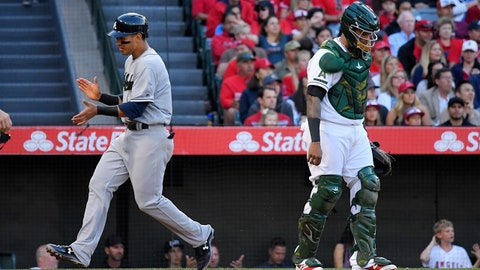 Atlanta Braves' Rio Ruiz, left, claps as he scores on a double by Danny Santana as Los Angeles Angels catcher Martin Maldonado stands at the plate during the third inning of a baseball game, Monday, May 29, 2017, in Anaheim, Calif. (AP Photo/Mark J. Terrill)