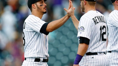 Colorado Rockies third baseman Nolan Arenado, left, and first baseman Mark Reynolds celebrate after the Rockies defeated the Cleveland Indians 8-1 in a baseball game Wednesday, June 7, 2017, in Denver. (AP Photo/David Zalubowski)