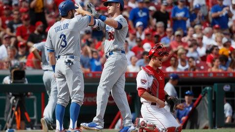 Los Angeles Dodgers' Cody Bellinger (35) celebrates his two-run home run alongside Chris Taylor (3) as Cincinnati Reds catcher Devin Mesoraco mans home plate in the third inning of a baseball game, Saturday, June 17, 2017, in Cincinnati. (AP Photo/John Minchillo)