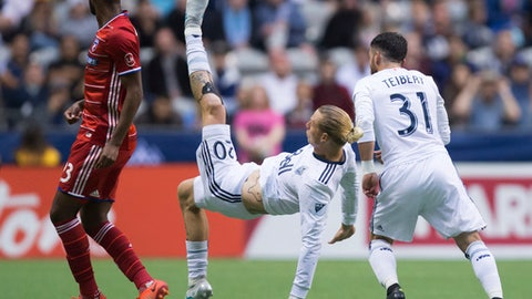 Vancouver Whitecaps' Brek Shea, center, falls to the ground between FC Dallas' Kellyn Acosta, left, and Vancouver's Russell Teibert during the first half of an MLS soccer match in Vancouver, British Columbia, Saturday, June 17, 2017. (Darryl Dyck/The Canadian Press via AP)
