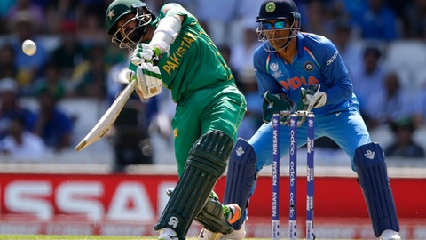 Pakistan batsman Azhar Ali hits the ball for six runs as India's wicketkeeper MS Dhoni, right, watches during the ICC Champions Trophy final between Pakistan and India at the Oval in London, Sunday, June 18, 2017. (AP Photo/Alastair Grant)