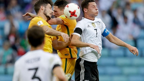 Germany's Julian Draxler, right, fight an aerial duel wit two Australian players during the Confederations Cup, Group B soccer match between Australia and Germany, at the Fisht Stadium in Sochi, Russia, Monday, June 19, 2017. (AP Photo/Thanassis Stavrakis)
