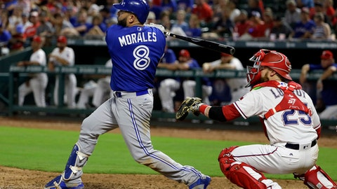 Toronto Blue Jays' Kendrys Morales follows through on a run-scoring single as Texas Rangers' Jonathan Lucroy, right, watches in the ninth inning of a baseball game, Monday, June 19, 2017, in Arlington, Texas. The hit that scored Josh Donaldson gave the Blue Jays the 7-6 lead and win. (AP Photo/Tony Gutierrez)