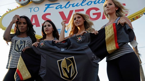 Models unveil the Vegas Golden Knights' new hockey jersey Tuesday, June 20, 2017, in Las Vegas. The Knights are an NHL hockey expansion team. (AP Photo/John Locher)