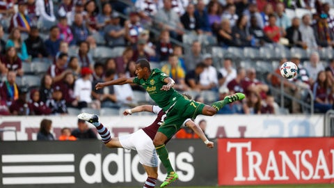 Portland Timbers defender Roy Miller (7) collides with Colorado Rapids forward Kevin Doyle (9) in the first half of an MLS soccer match Saturday, June 17, 2017, in Commerce City, Colo. (AP Photo/David Zalubowski)