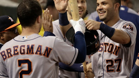 Houston Astros' Jose Altuve, right, celebrates with Alex Bregman (2) after scoring against the Oakland Athletics during the sixth inning of a baseball game Wednesday, June 21, 2017, in Oakland, Calif.  (AP Photo/Ben Margot)