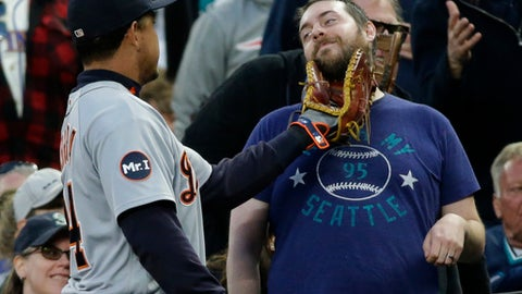 Detroit Tigers first baseman Miguel Cabrera, left, playfully touches the beard of a Seattle Mariners' fan with his glove after Cabrera followed a foul ball that went into the stands in the sixth inning of a baseball game, Wednesday, June 21, 2017, in Seattle. The Mariners won 7-5. (AP Photo/Ted S. Warren)