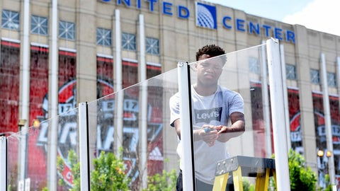 Serell Williams works on a street hockey rink for the NHL Centennial Fan Arena outside the United Center as preparation for the NHL Draft continue, Thursday, June 22, 2017, in Chicago. The two day draft begins Friday. (AP Photo/G-Jun Yam)