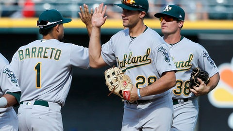 The Oakland Athletics Franklin Barreto (1) Matt Olson, center, and Jaycob Brugman celebrate a win over the Chicago White Sox after a baseball game Saturday, June 24, 2017, in Chicago. (AP Photo/Charles Rex Arbogast)