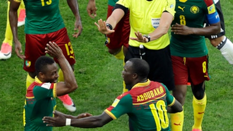 Referee Wilmar Roldan center gestures as he is surrounded by Cameroon's players during the Confederations Cup Group B soccer match between Germany and Cameroon at the Fisht Stadium in Sochi Russia Sunday