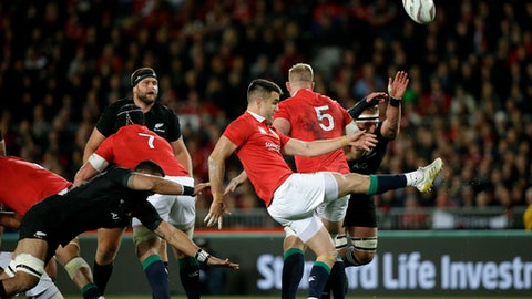 In this Saturday June 24, 2017 photo, Lions scrumhalf Conor Murray kicks the ball as New Zealand loose forward Jerome Kaino dives during the first test between the British and Irish Lions and the All Blacks at Eden Park in Auckland, New Zealand. Rival coaches Warren Gatland and Steve Hansen clashed Monday, June 26, 2017 after the British and Irish Lions' head coach claimed that New Zealand players set out to injure scrumhalf Conor Murray in the first rugby test at Auckland on Saturday. (AP Photo/Mark Baker)
