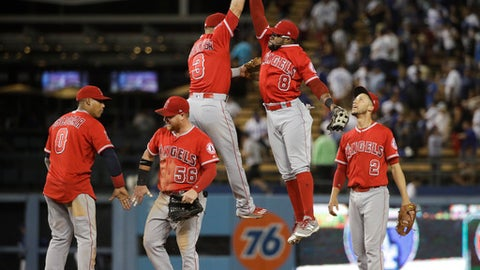 Los Angeles Angels' Eric Young Jr., second from left, and Danny Espinosa jump in the air as they celebrate their team's 4-0 win against the Los Angeles Dodgers in a baseball game, Monday, June 26, 2017, in Los Angeles. (AP Photo/Jae C. Hong)