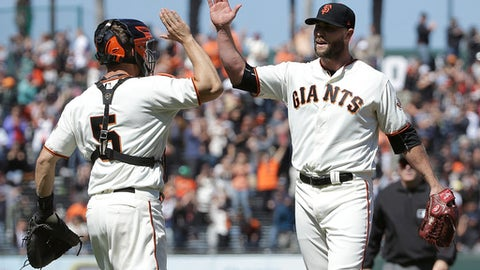 San Francisco Giants catcher Nick Hundley (5) and pitcher Hunter Strickland celebrate after the Giants defeated the Colorado Rockies 5-3 in a baseball game in San Francisco, Wednesday, June 28, 2017. (AP Photo/Jeff Chiu)