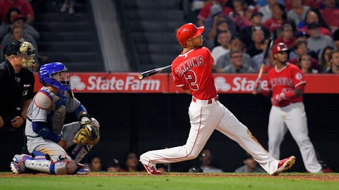 Los Angeles Angels' Andrelton Simmons watches his two-run home run in front of Los Angeles Dodgers catcher Yasmani Grandal during the sixth inning of a baseball game, Wednesday, June 28, 2017, in Anaheim, Calif. (AP Photo/Mark J. Terrill)