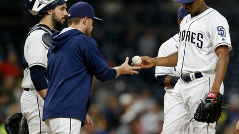 San Diego Padres manager Andy Green, front left, takes the ball from starting pitcher Luis Perdomo, with catcher Austin Hedges, left, watching during the sixth inning of the team's baseball game against the Atlanta Braves in San Diego, Wednesday, June 28, 2017. (AP Photo/Alex Gallardo)