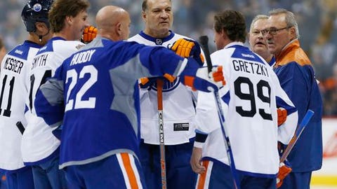 FILE - In this Oct. 21, 2016, file photo, former Edmonton Oilers hockey player Dave Semenko, center, and others listen in as captain Wayne Gretzky (99) leads a huddle during a practice for the NHL's Heritage Classic Alumni game in Winnipeg, Manitoba. Former Edmonton Oilers tough guy Dave Semenko, who protected Wayne Gretzky in the 1980s, has died. He was 59. The Oilers say Semenko died after a short battle with cancer. A team spokesman said Semenko died in Edmonton. (John Woods/The Canadian Press via AP, File)