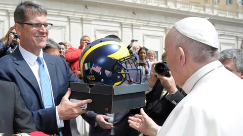 Pope Francis is presented with a football helmet by Michigan football team coach Jim Harbaugh during the weekly general audience at the Vatican, Wednesday, April 26, 2017. (L'Osservatore Romano/Pool Photo via AP)