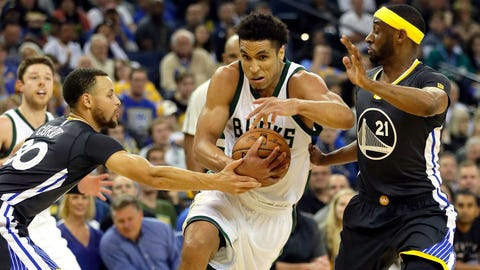 OAKLAND, CA - MARCH 18:  Malcolm Brogdon #13 of the Milwaukee Bucks drives to the basket as Stephen Curry #30 and Ian Clark #21 of the Golden State Warriors defend during the game at ORACLE Arena on March 18, 2017 in Oakland, California.  (Photo by Jamie Squire/Getty Images)