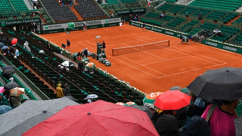 Workers prepare to cover the Philippe Chatrier court as the match between France's Richard Gasquet and France's Gael Monfils is interrupted due to rain during the Roland Garros 2017 French Open on June 3, 2017 in Paris.  / AFP PHOTO / GABRIEL BOUYS        (Photo credit should read GABRIEL BOUYS/AFP/Getty Images)