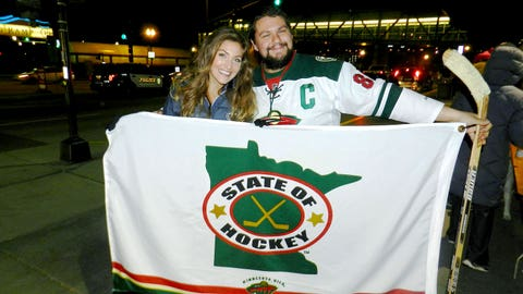 Jennifer and a fan wave the flag for the State of Hockey!