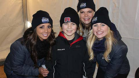 Chyna snaps a picture with a young hockey fan, along with Kaylin and Kendall of the FOX Sports North Girls.