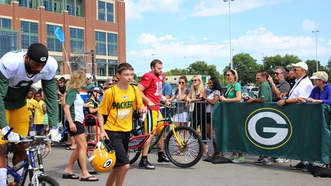 Chyna, Sage and Bishara watch the Packers head to practice via borrowed bicycles.