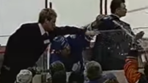 Tie Domi sprays water at fans over the glass (March 2001)