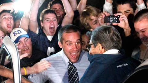 Students greet Penn State coach Joe Paterno as he arrives at his home