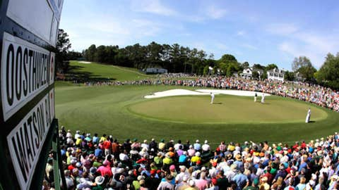 In a photo taken with a fisheye lens, Louis Oosthuizen, right, of South Africa, watches as Bubba Watson putts