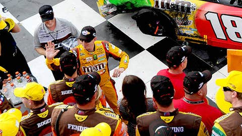 Kyle Busch, driver of the #18 M&M's Toyota, celebrates in victory lane with his team after winning during the NASCAR Sprint Cup Series Cheez-It 355