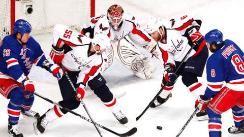 New York Rangers left wing Ruslan Fedotenko (26) and right wing Brandon Prust (8) battle for the puck with Washington Capitals defenseman Jeff Schultz