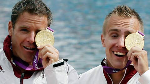 Hungary's Rudolf Dombi , right, and Roland Kokeny celebrate at the podium after winning the gold medal
