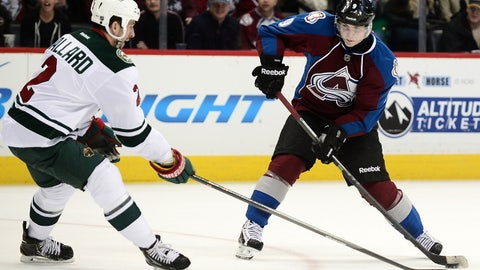 Jan 30, 2014; Denver, CO, USA; Colorado Avalanche center Matt Duchene (9) skates with the puck in front of Minnesota Wild defenseman Keith Ballard (2) in the second period at the Pepsi Center. Mandatory Credit: Ron Chenoy-USA TODAY Sports
