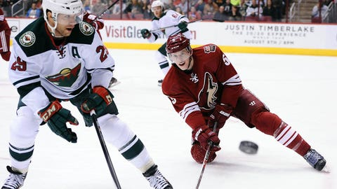 Jan 9, 2014; Glendale, AZ, USA; Phoenix Coyotes defensemen Connor Murphy (5) watches the puck against the Minnesota Wild forward Jason Pominville (29) in the first period at Jobing.com Arena. Mandatory Credit: Jennifer Stewart-USA TODAY Sports