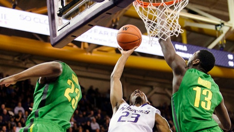 Jan 23, 2014; Seattle, WA, USA; Washington Huskies guard C.J. Wilcox (23) shoots a layup but is blocked by Oregon Ducks forward Richard Amardi (13) during the first half at Alaska Airlines Arena at Hec Edmundson Pavili. Mandatory Credit: Steven Bisig-USA TODAY Sports