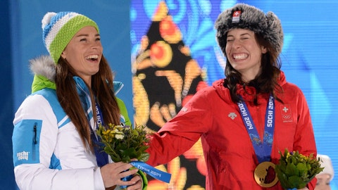 Feb 12, 2014; Sochi, RUSSIA; Co-gold medal winners Tina Maze (SLO), left, and Dominique Gisin (GUI) react during the medal ceremony for the ladies' alpine skiing downhill the Sochi 2014 Olympic Winter Games at the Medals Plaza. Mandatory Credit: James Lang-USA TODAY Sports