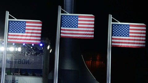 Feb 13, 2014; Sochi, RUSSIA; A general view as three American flags are raised in front of the Olympic cauldron during the medal ceremony for the men's ski slopestyle at the Sochi 2014 Olympic Winter Games at the Medals Plaza. The flags represent medals won by Joss Christensen , Gus Kenworthy and Nicholas Goepper. Mandatory Credit: James Lang-USA TODAY Sports