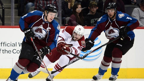 Feb 28, 2014; Denver, CO, USA; Phoenix Coyotes left wing Mikkel Boedker (89) passes against Colorado Avalanche left wing Gabriel Landeskog (92) and defenseman Nate Guenin (5) in the first period at the Pepsi Center. Mandatory Credit: Ron Chenoy-USA TODAY Sports
