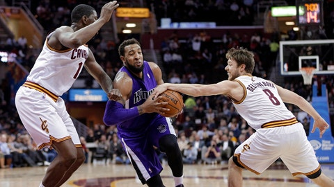 Cleveland Cavaliers' Matthew Dellavedova (8), from Australia, strips the ball from Sacramento Kings' Derrick Williams, center, as Henry Sims, left, moves in to help during the second quarter of an NBA basketball game Tuesday, Feb. 11, 2014, in Cleveland. (AP Photo/Mark Duncan)
