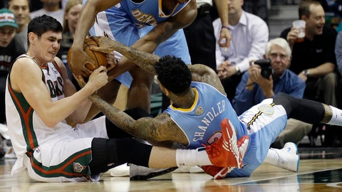 Denver Nuggets' Wilson Chandler (21) and Milwaukee Bucks' Ersan Ilyasova, left, reach for a loose ball during the first half of an NBA basketball game Thursday, Feb. 20, 2014, in Milwaukee. (AP Photo/Jeffrey Phelps)