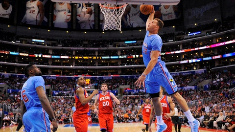 Los Angeles Clippers forward Blake Griffin, right, goes up for a dunks as teammate center DeAndre Jordan, left, stands near along with Philadelphia 76ers guard Hollis Thompson, second from left, and center Spencer Hawes, third from left, during the first half of an NBA basketball game, Sunday, Feb. 9, 2014, in Los Angeles. (AP Photo/Mark J. Terrill)