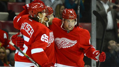 Jan 22, 2014; Detroit, MI, USA; Detroit Red Wings defenseman Danny DeKeyser (65), center Gustav Nyquist (14) and left wing Justin Abdelkader (8) celebrate after a goal during the second period against the Chicago Blackhawks at Joe Louis Arena. Mandatory Credit: Andrew Weber-USA TODAY Sports
