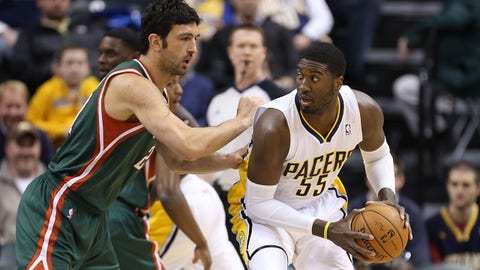 Feb 27, 2014; Indianapolis, IN, USA; Indiana Pacers center Roy Hibbert (55) dribbles the ball as Milwaukee Bucks center Zaza Pachulia (27) defends at Bankers Life Fieldhouse. Mandatory  Credit: Brian Spurlock-USA TODAY Sports