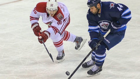 Feb 27, 2014; Winnipeg, Manitoba, CAN; Winnipeg Jets defenseman Zach Bogosian (44) battles for the puck with Phoenix Coyotes forward Mikkel Boedker (89) during the third period at MTS Centre. The Jets won 3-2 in overtime. Mandatory Credit: Bruce Fedyck-USA TODAY Sports