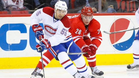 Feb 8, 2014; Raleigh, NC, USA; Montreal Canadiens defensemen Francis Bouillon (55) carries the puck past the Carolina Hurricanes forward Alexander Semin (28) during the 2nd period at PNC Arena. Mandatory Credit: James Guillory-USA TODAY Sports