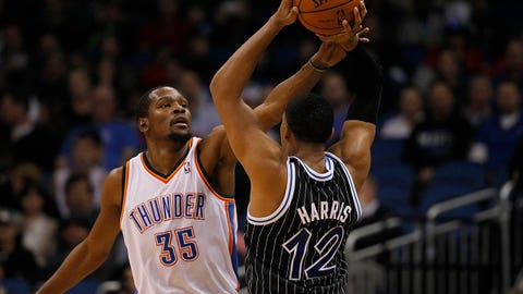 Feb 7, 2014; Orlando, FL, USA; Orlando Magic small forward Tobias Harris (12) holds the ball as Oklahoma City Thunder small forward Kevin Durant (35) defends during the first half at Amway Center. Mandatory Credit: Kim Klement-USA TODAY Sports