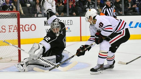 Feb 3, 2014; Los Angeles, CA, USA; Los Angeles Kings goalie Jonathan Quick (32) blocks a shot against Chicago Blackhawks left wing Patrick Sharp (10) during the second period at Staples Center. Mandatory Credit: Gary A. Vasquez-USA TODAY Sports